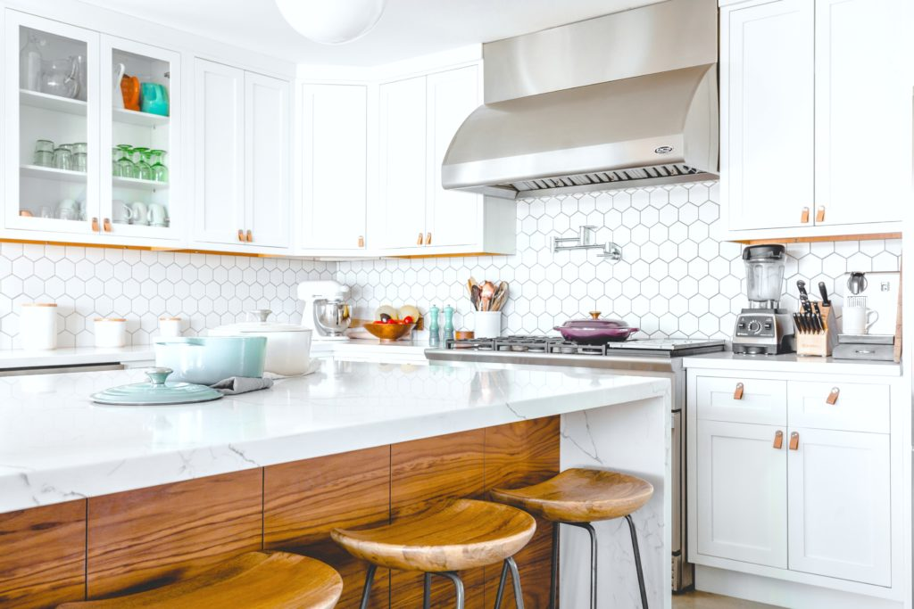 A white and rustic kitchen is mixed with modern touches and warmth from wood.