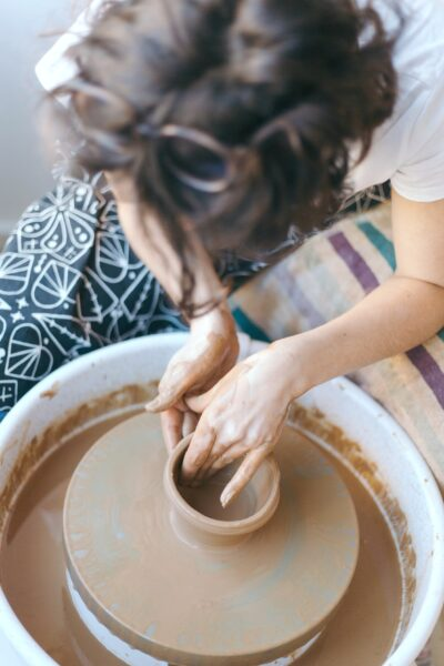 Woman is bending over pottery wheel, enthralled with doing her art.