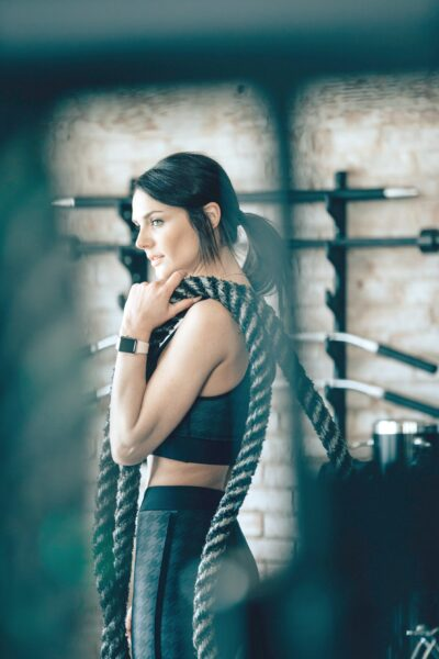 Woman holding battle ropes in her home gym.