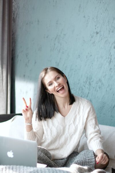 A woman gives a peace sign as she sits happily in bed on her laptop.