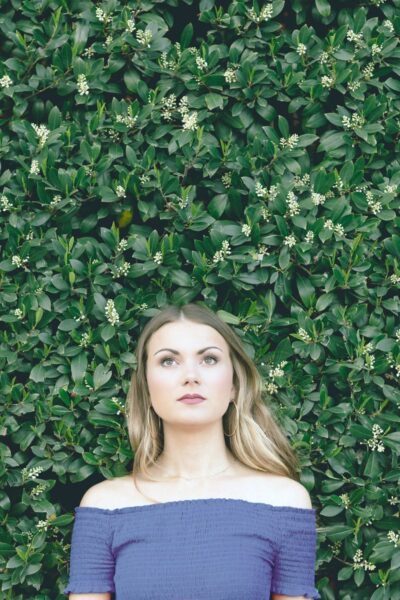 Woman stands in front of a green live plant wall, looks up pensively