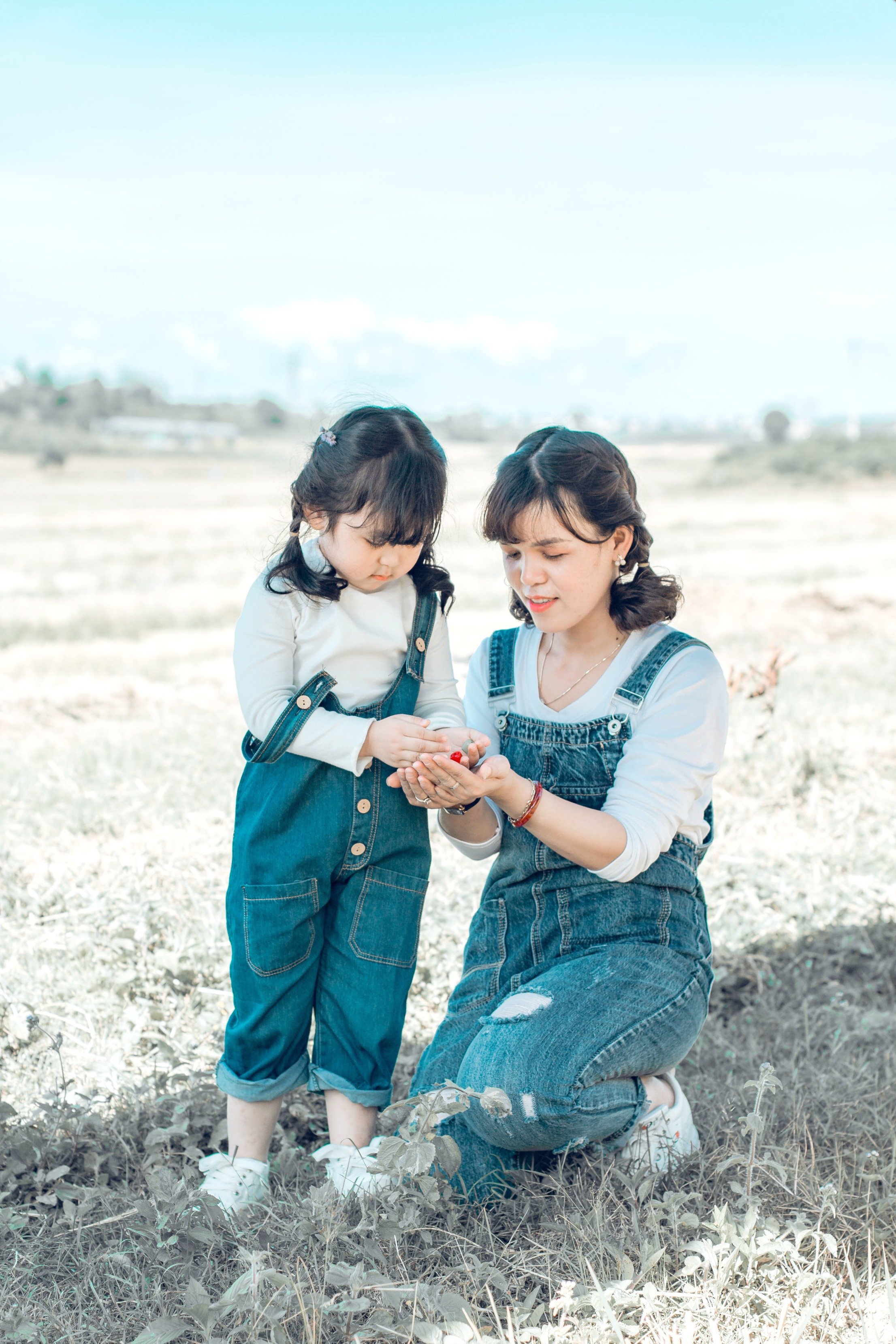 A mother is in a field with her young daughter.