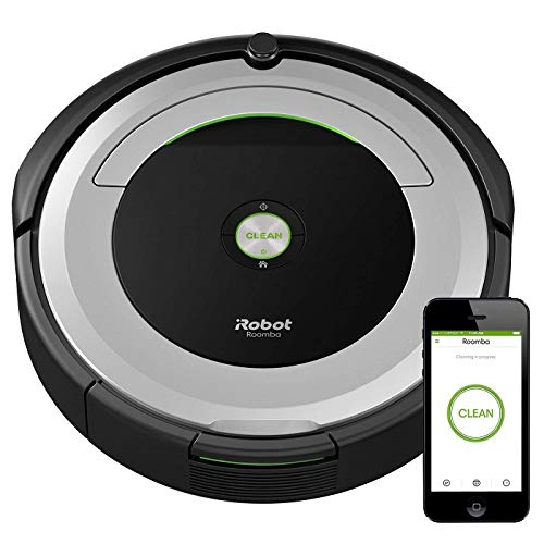 An iRobot Roomba with a phone showing it connected to the vacuum.