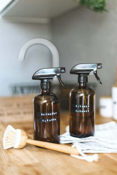Two cleaning bottles for the Kitchen and Bathroom sit on a countertop with a cleaning brush.