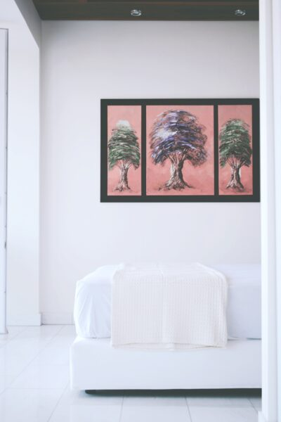 A bedroom that features the end of a mattress and bed, pretty artwork is behind it against a white wall.