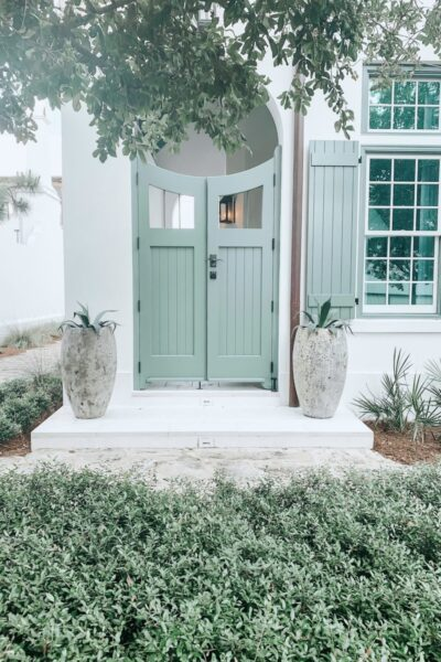 A beautiful white house with a green door, two potted plants are next to the doorway.