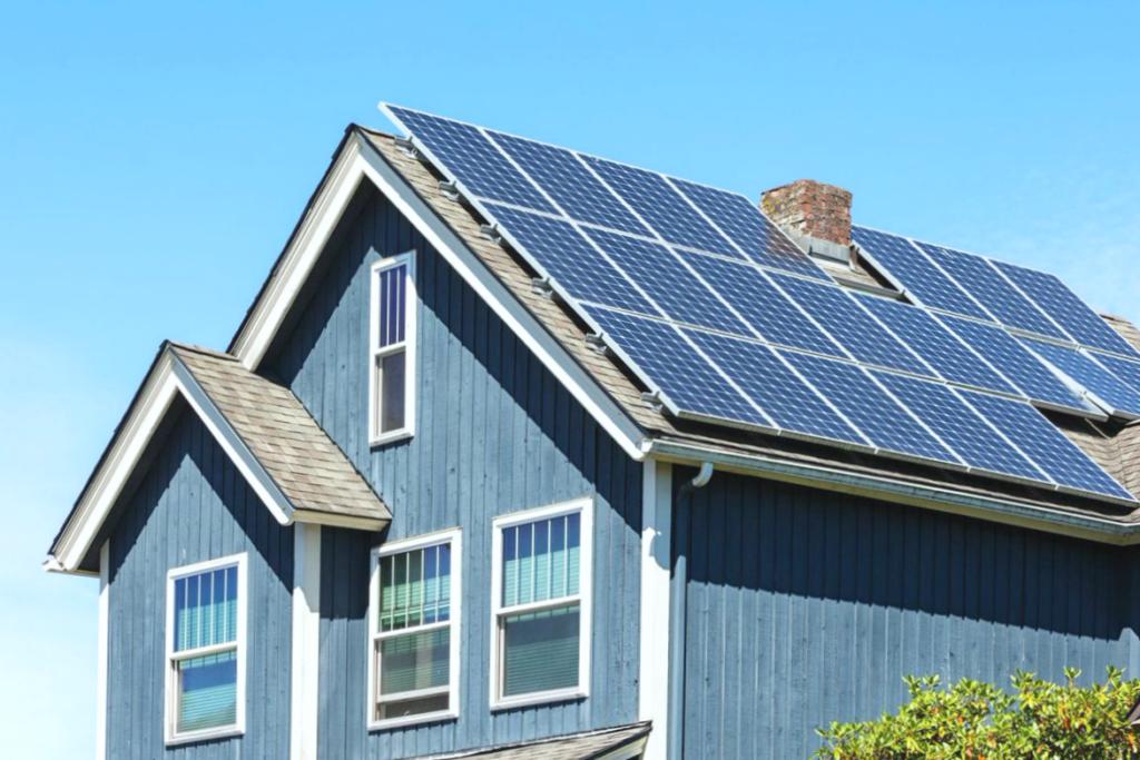 A nice suburban home with solar panels, against a blue sky.