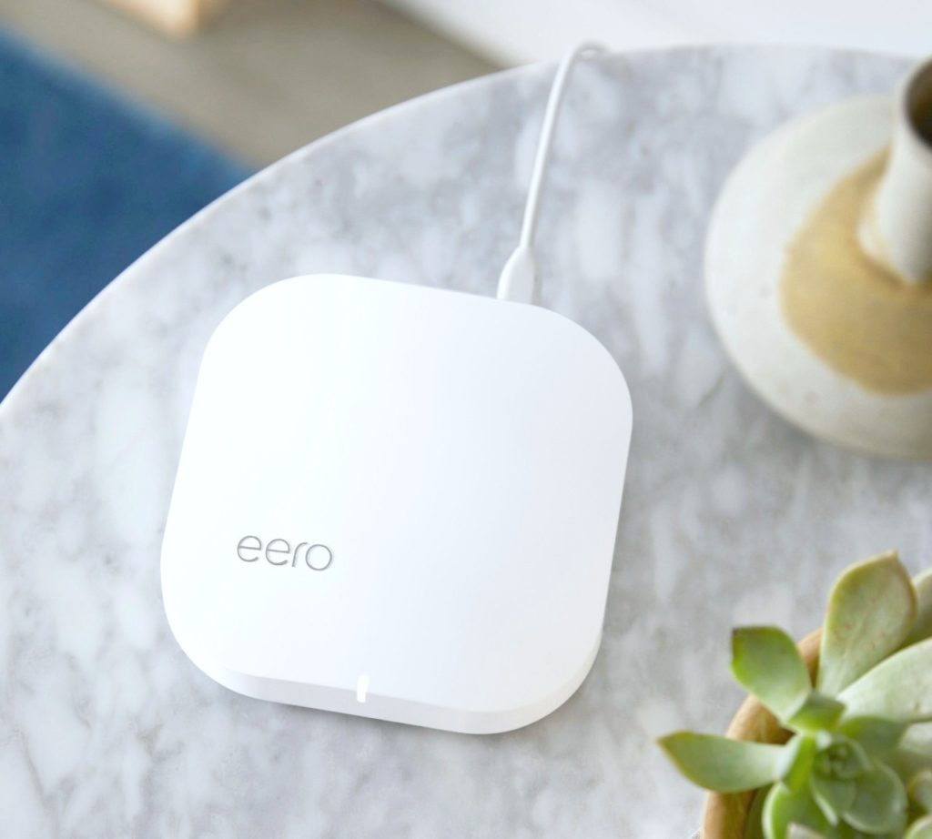 A flat lay of an Eero on a grey marble table.