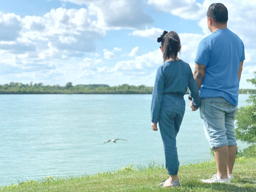 Mimi and Darasak watch a bird fly over the Detroit river while standing on a hillside.
