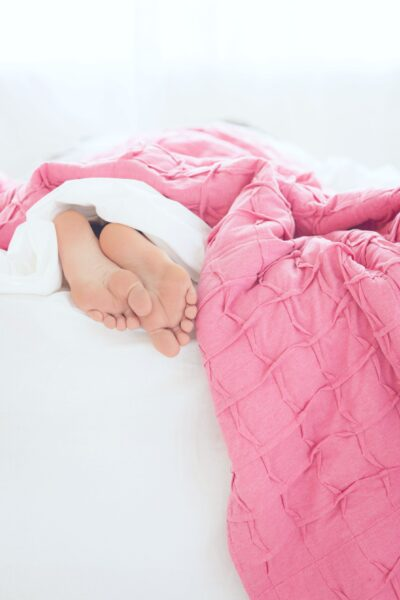 Feet hang out the bottom of the bed under a pink blanket.