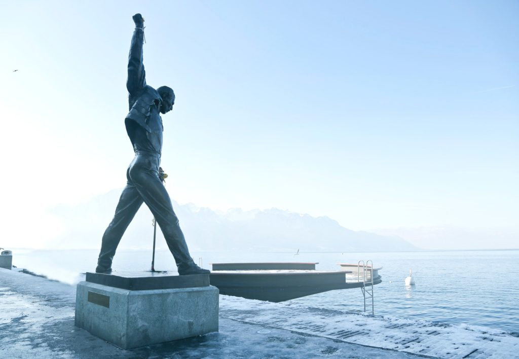 A statue of Freddie Mercury stands in his signature pose alongside a body of water, the sky is behind him.