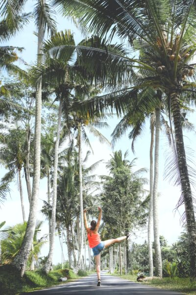 Palm trees are shown, a woman in the center of two rows of them jumps in the air.