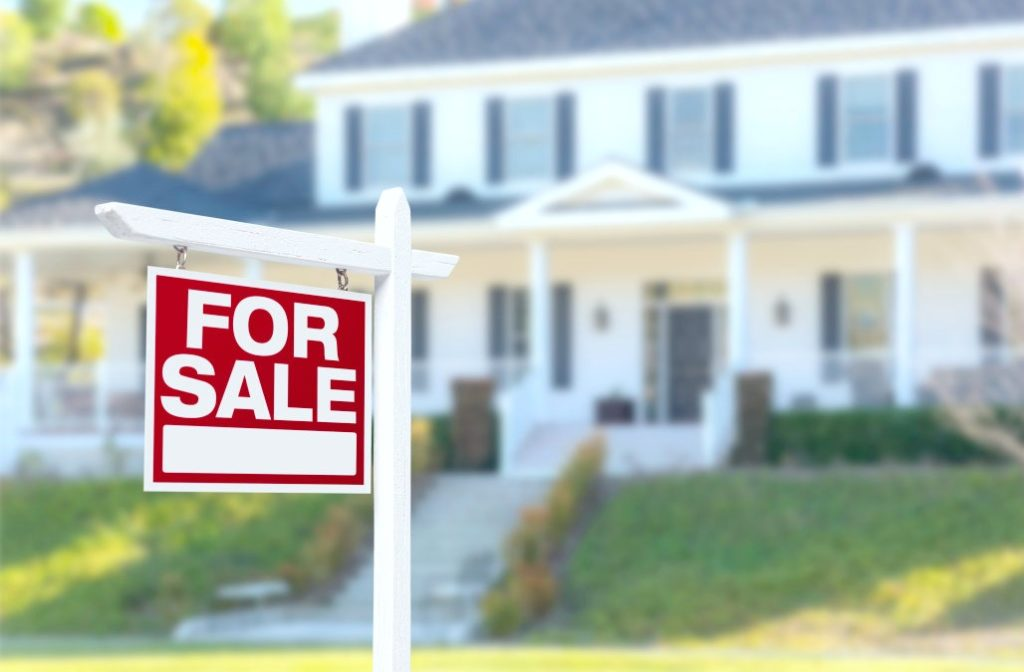 A for sale sign is shown in front of a beautiful starter home, it is blurred in the background.