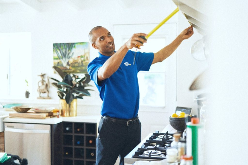 A Best Buy consultant measures a space in a client's home.