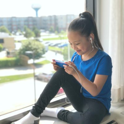 Mimi sits on a ledge at a hotel and watches YouTube.