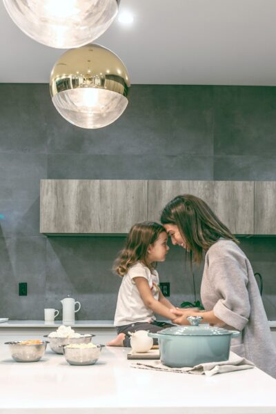 Mother and child in kitchen, touch foreheads, they're very happy.