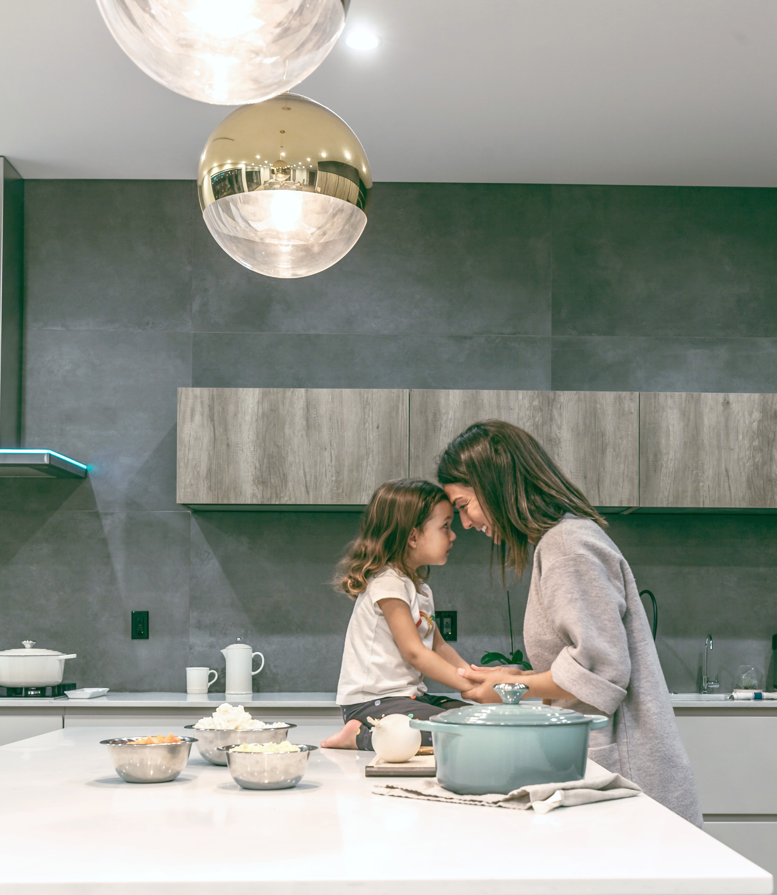 Mother and child in kitchen, touch foreheads, they're very happy. Making your home pretty will help to increase the feel-good factors in your home.