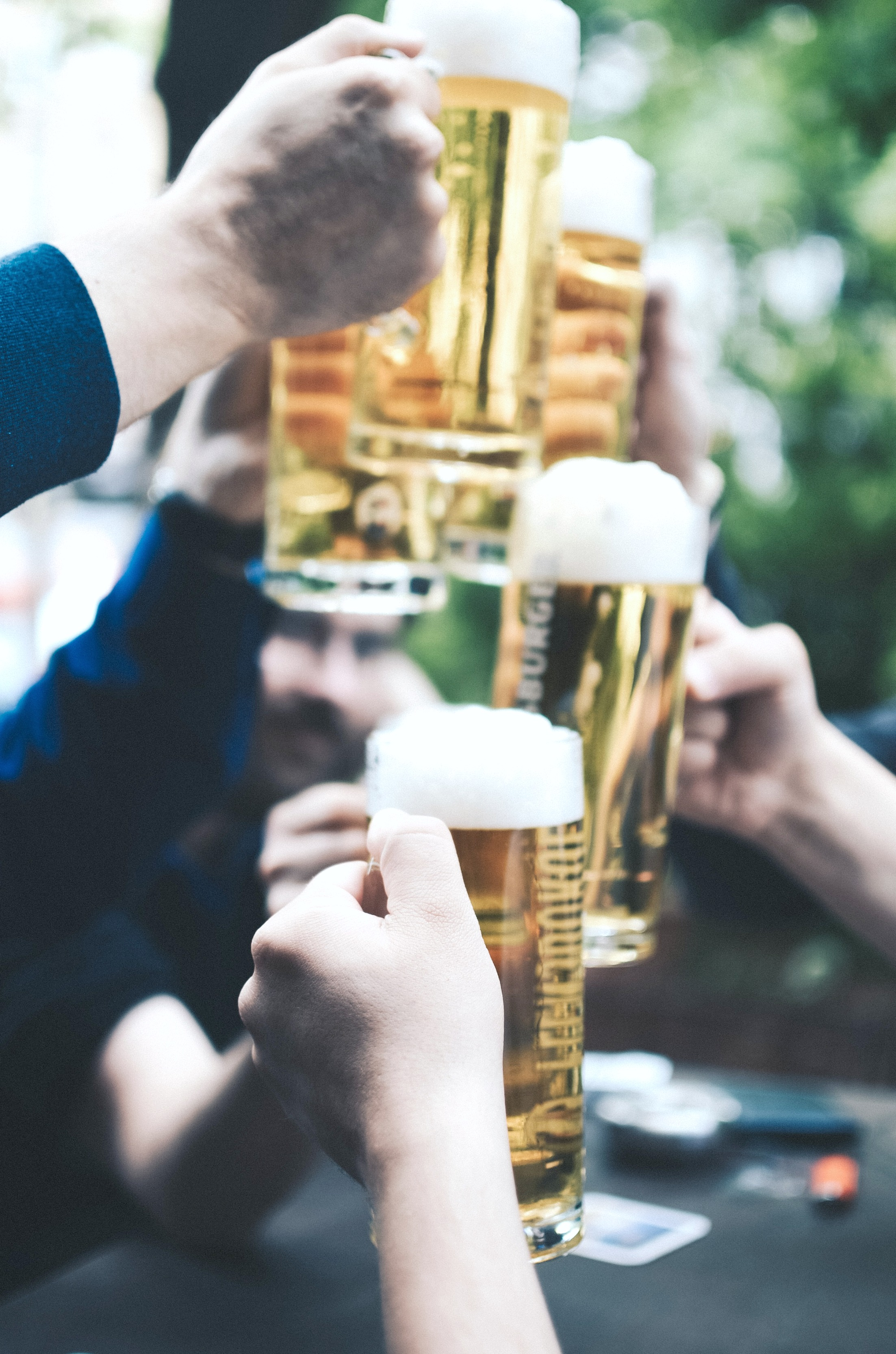A group of men hold up pints of beer and cheer a good night out.