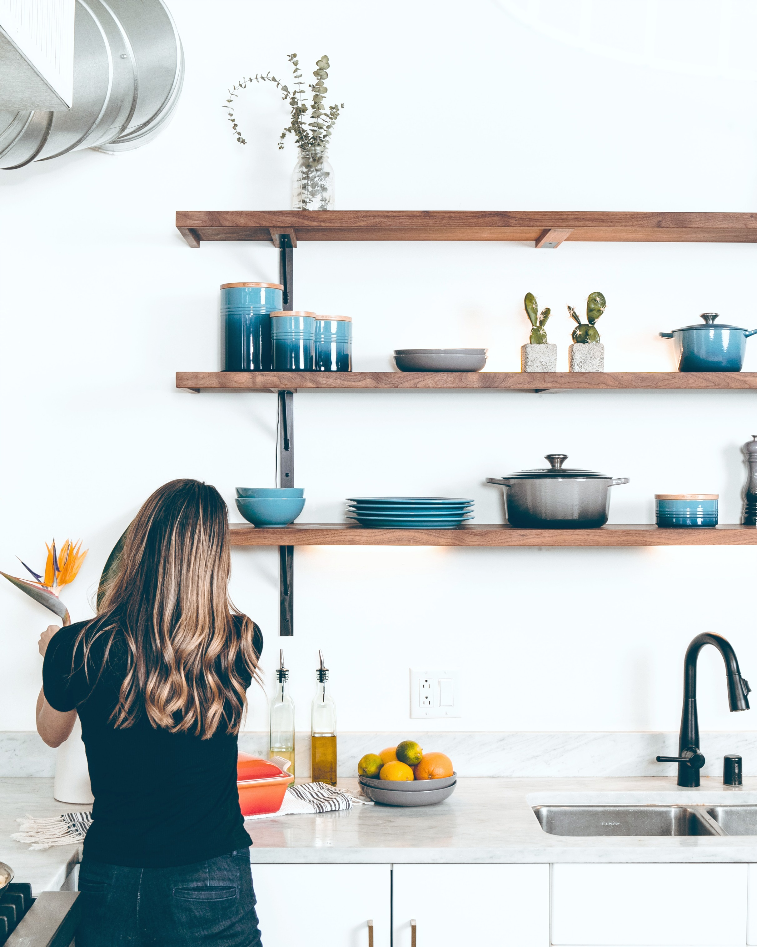 A woman adds flowers to her beautiful modern kitchen. The kitchen has exposed shelves.