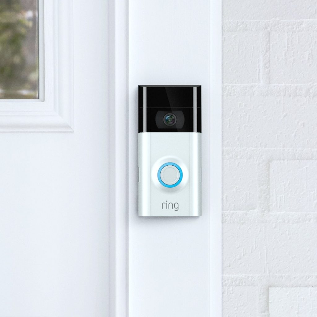 A close up of a ring doorbell is attached to a door pane.