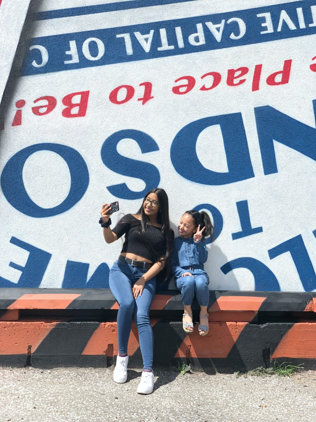 Two sisters, Gabby and Mimi, take a selfie in front of a murale in Downtown Windsor. See how TELUS can help keep families connected.