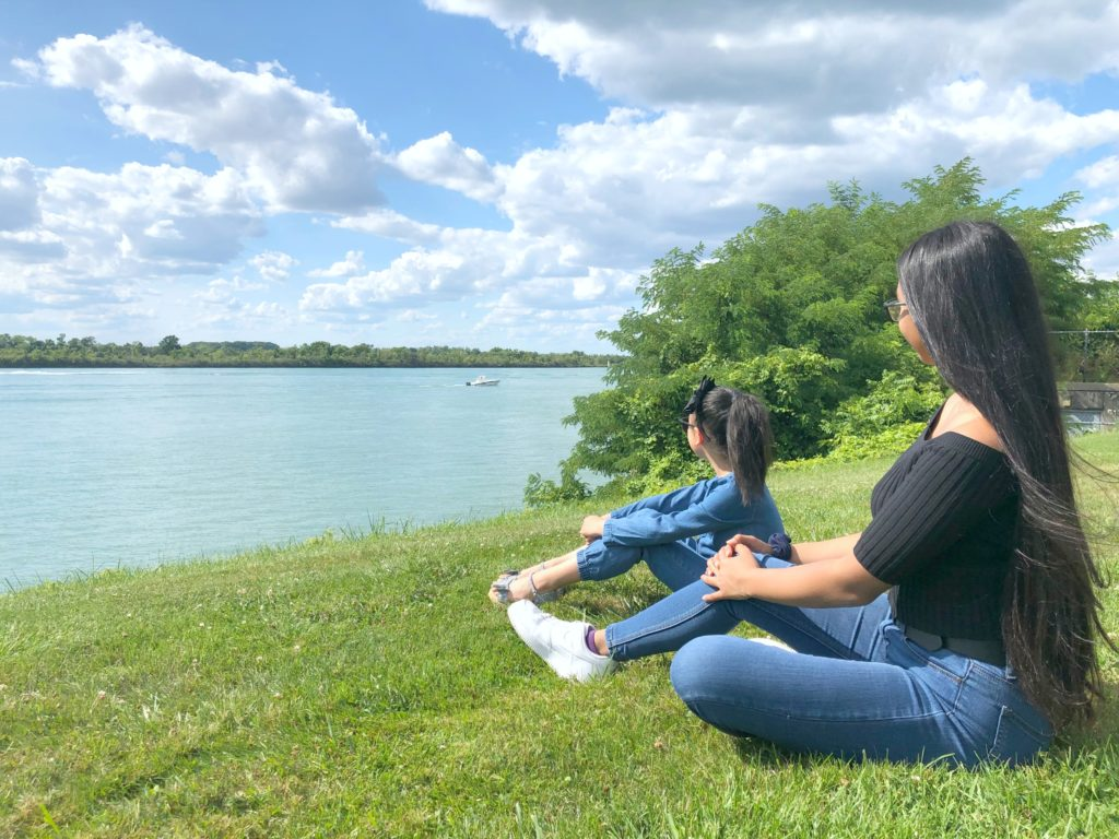 Gabby and Mimi sit on a hill side by the Detroit river, they're watching boats go by.