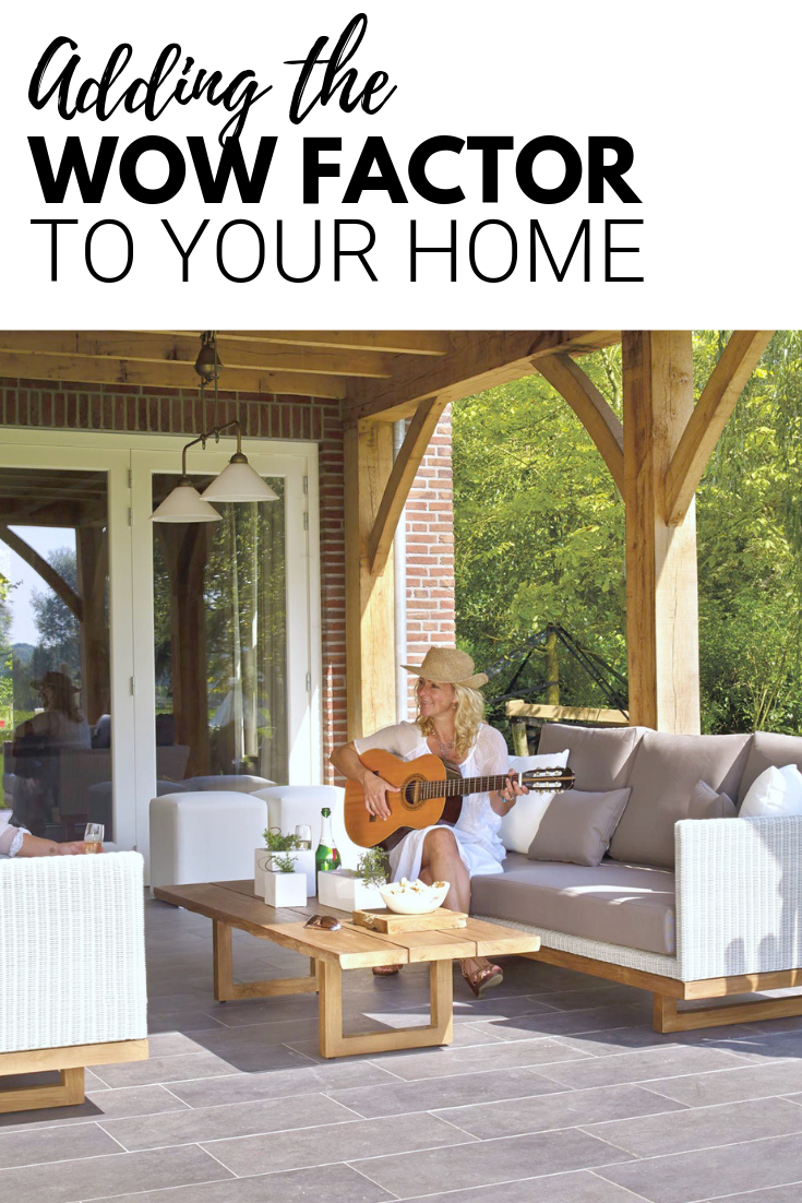 "A banner reads, ""Adding the Wow Factor to your Home,"" a picture of Two women sitting on a patio, the patio has lovely rattan sofas and two women sit on each sofa. One is playing guitar."