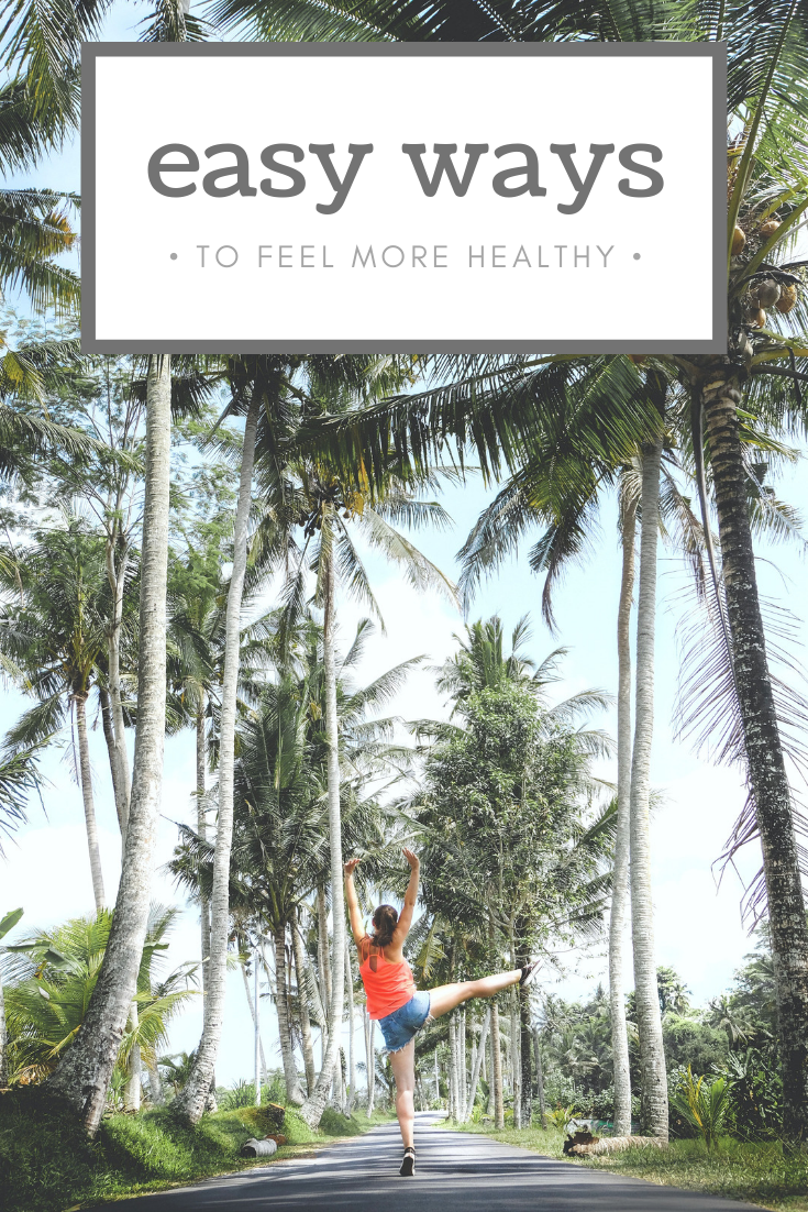 "A banner reads, ""Easy Ways to Feel Healthier,"" the whole picture is seen of a two rows of tall palm trees and a woman in the center is jumping in the air."