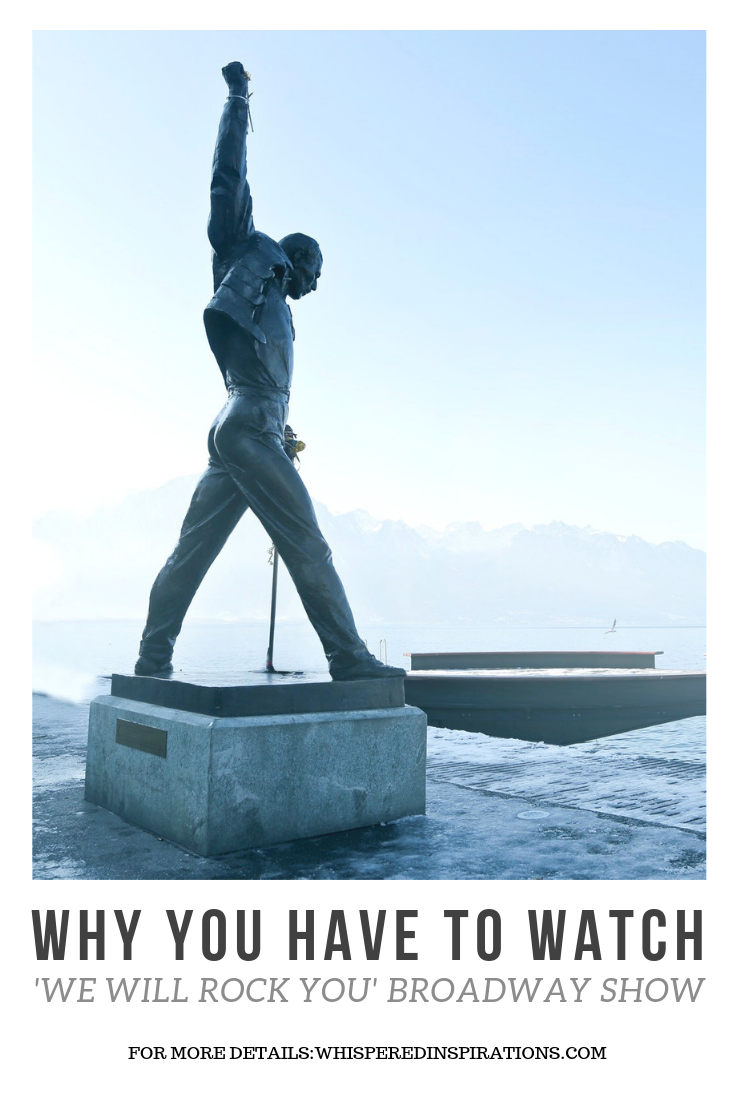 "A statue of Freddie Mercury stands in his signature pose alongside a body of water, the sky is behind him. Below, a banne reads, ""Have you watched the brodadway show 'We Will Rock You' yet?"