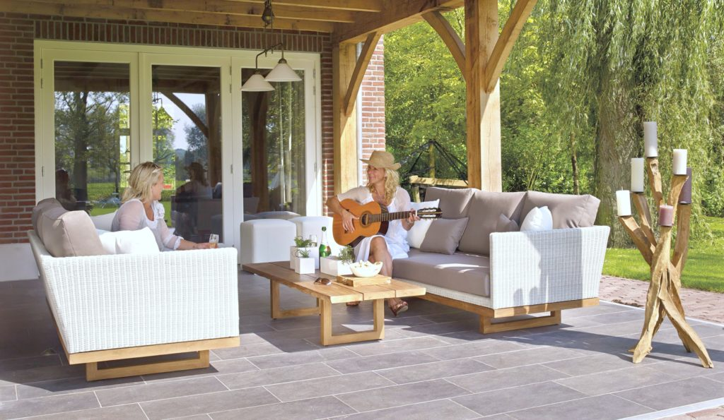 Two women sitting on a patio, the patio has lovely rattan sofas and two women sit on each sofa. One is playing guitar.
