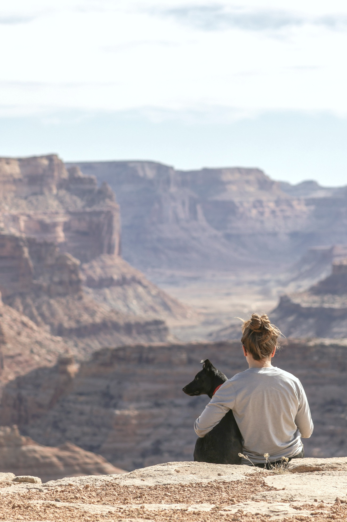 Woman sits at the edge of the Grand Canyon with her dog. The vast is seen. This is how you leave your comfort zone when you're on vacation.