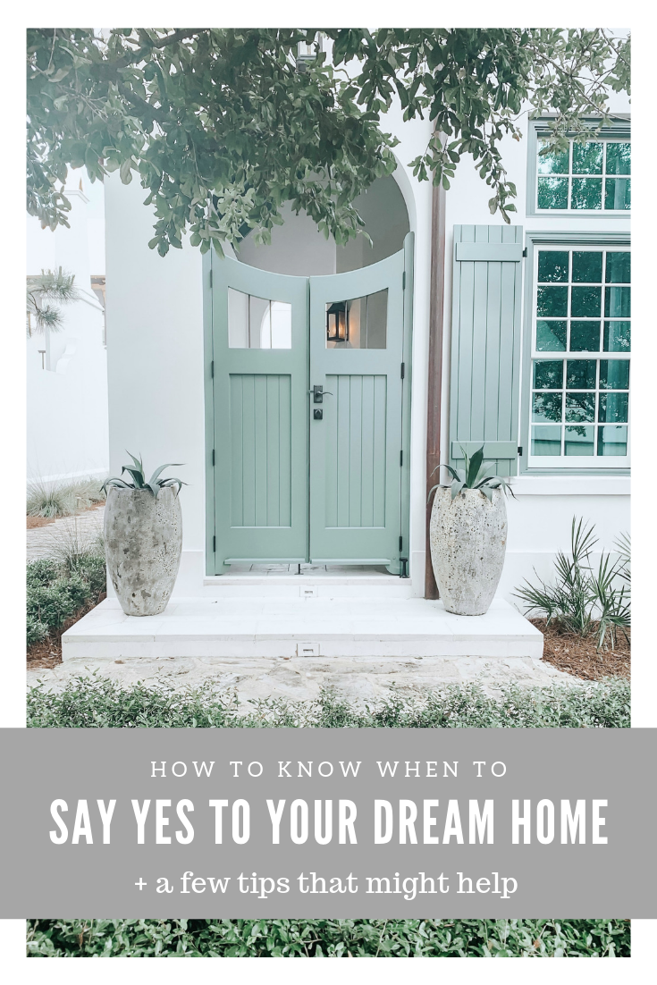 "A beautiful white house with a green door, two potted plants are next to the doorway. A banner on top reads, ""How to know when to say yes to your dream home + tips that can help."""