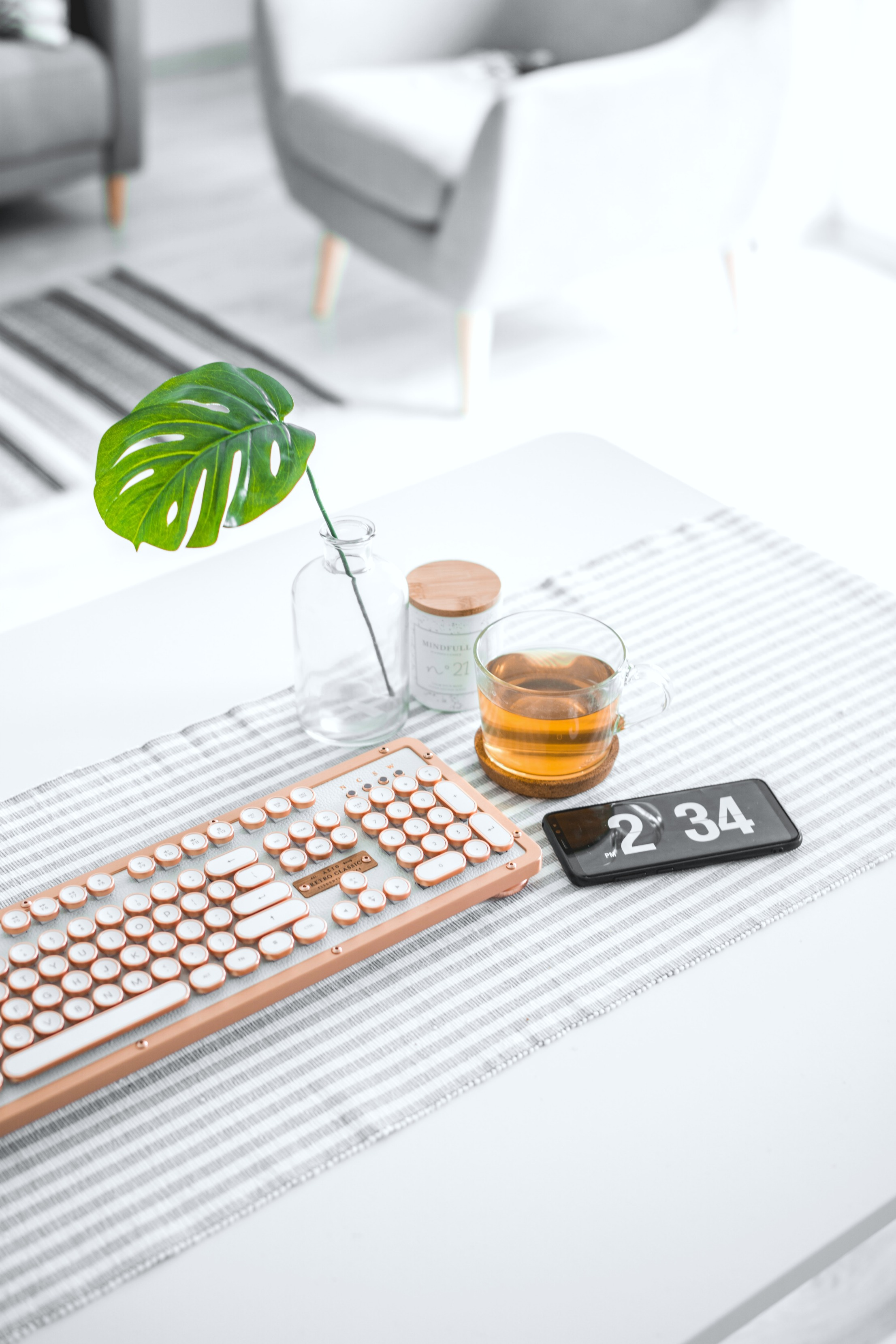 A desk with a plant, a cup of tea, keyboard, and phone are seen. A living room is in the background.