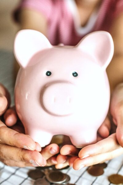 A couple and their daughter hold a piggy bank together. Coins surround the piggy bank.