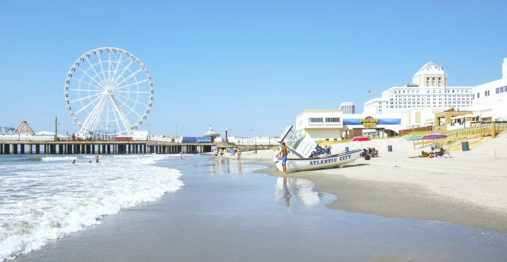 "The beach with the pier in Atlantic City in the back. A person is shown with a boat that says, ""Atlantic City."""