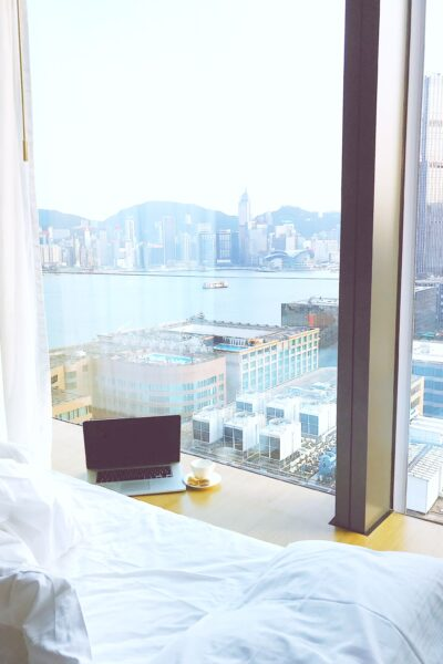 Empty bed with laptop, over looking a city through a hotel room.
