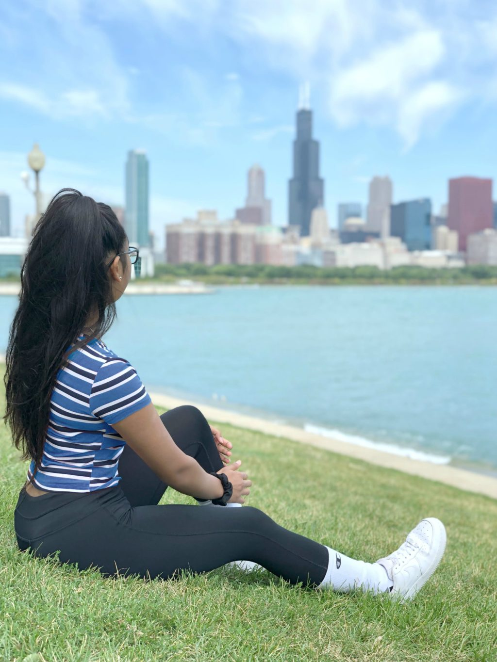 Gabby sitting by Lake Michigan overlooking the Chicago skyline.