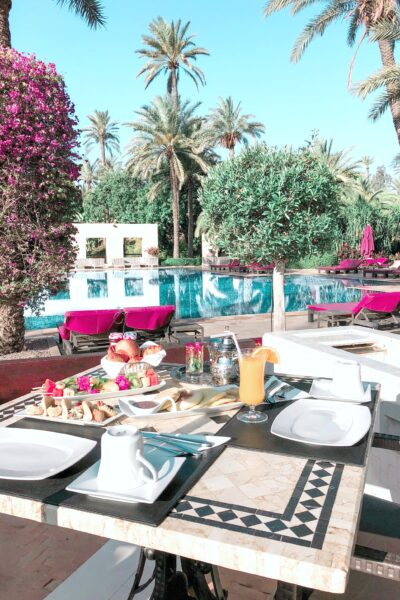 A luxury hotel pool with a table filled with food.