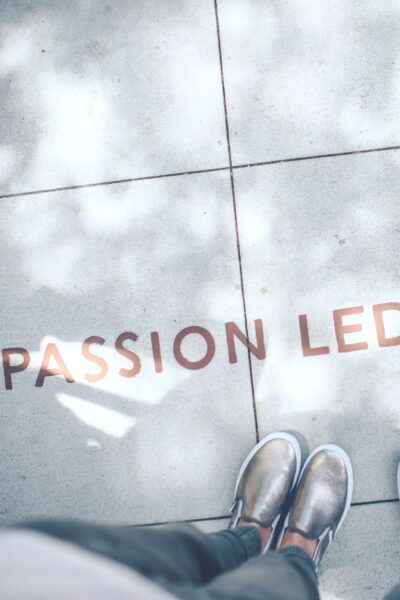 "Two people starting their careers stand in front of a quote that says, ""passion led us here."""
