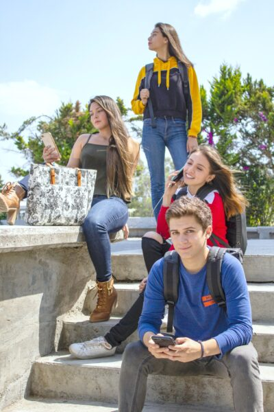 A group of teenagers sitting on a stairs on their phones and chilling on campus.