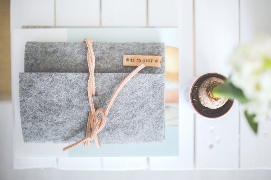 """Grey agenda that says """"to-do"""" list on a white wood table, a flower is seen from a bird's eye view. The agenda is to keep track of tasks that you really need to stop putting off."""