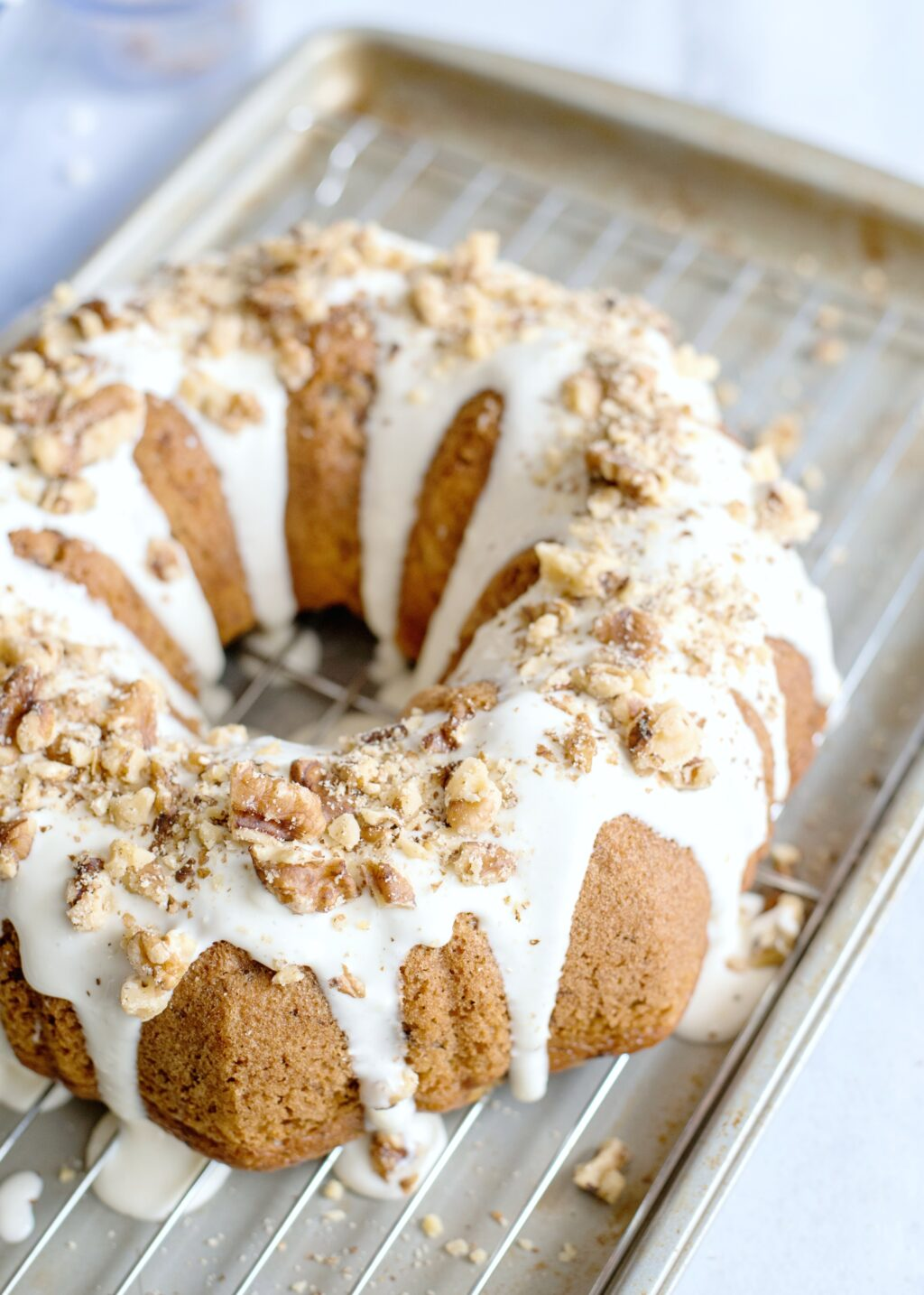 Bundt cake being drizzled with glaze and walnuts.