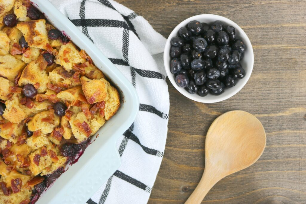 A pan of Blueberry Bacon Bread Pudding shown with a napkin, wooden spoon, and small bowl of blueberries. They are birds eye view against a wood counter.