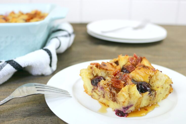 A pan of Blueberry Bacon Bread pudding is on a small plate, maple syrup is drizzled on top with a fork.