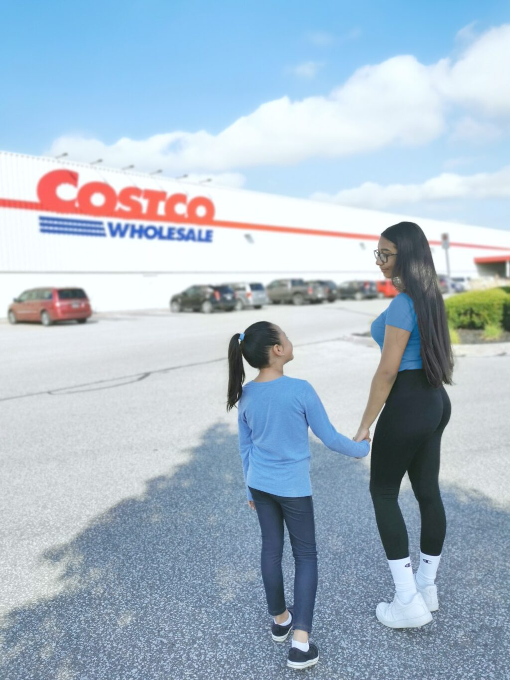 Gabby and Mimi walking into Costco Wholesale, they hold hands and smile.