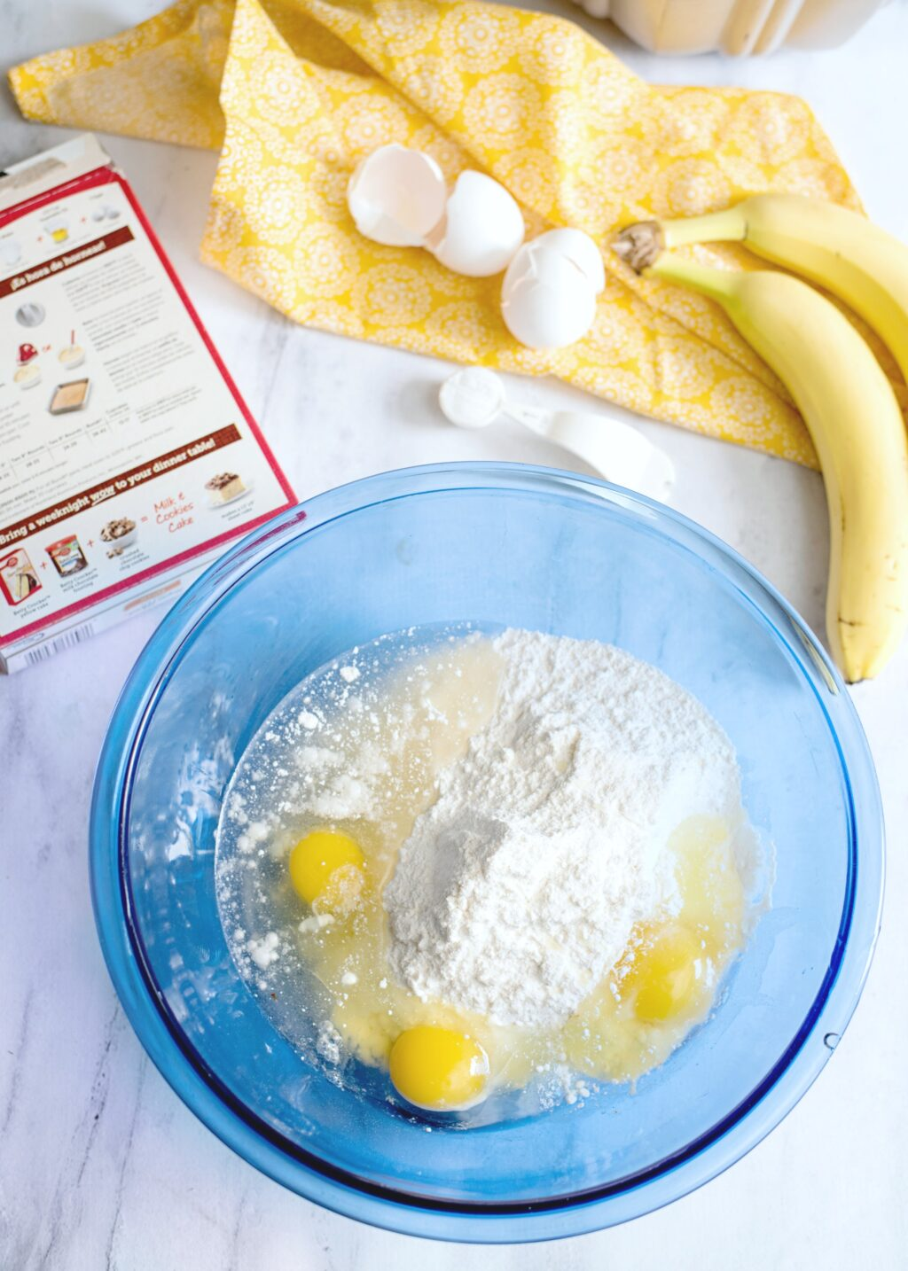 A blue bowl with wet and dry baking ingredients. Banana and eggs rest on a napkin.