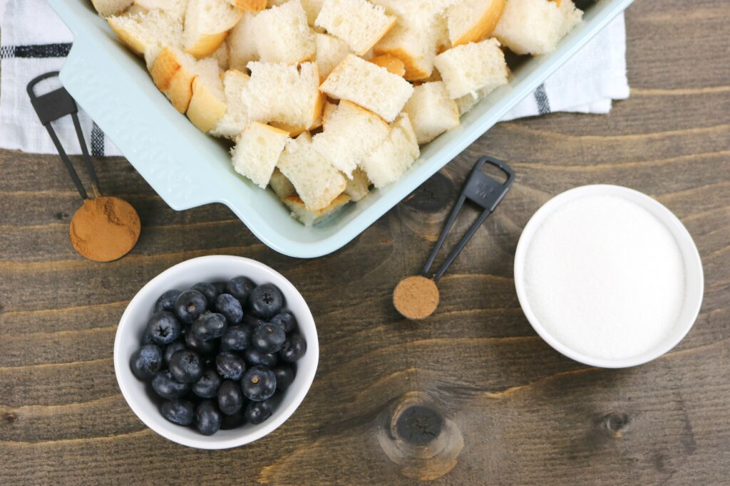 9x13 baking pan with cubed bread. Ingredients like cinnamon, nutmeg, sugar, and blueberries surround it.