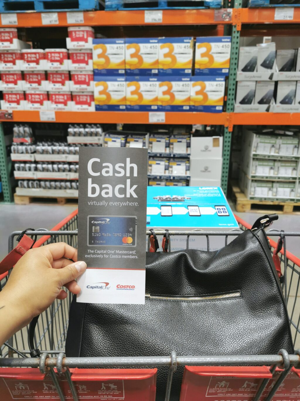Nancy holds a brochure for Capital One's Costco credit card while she shops.