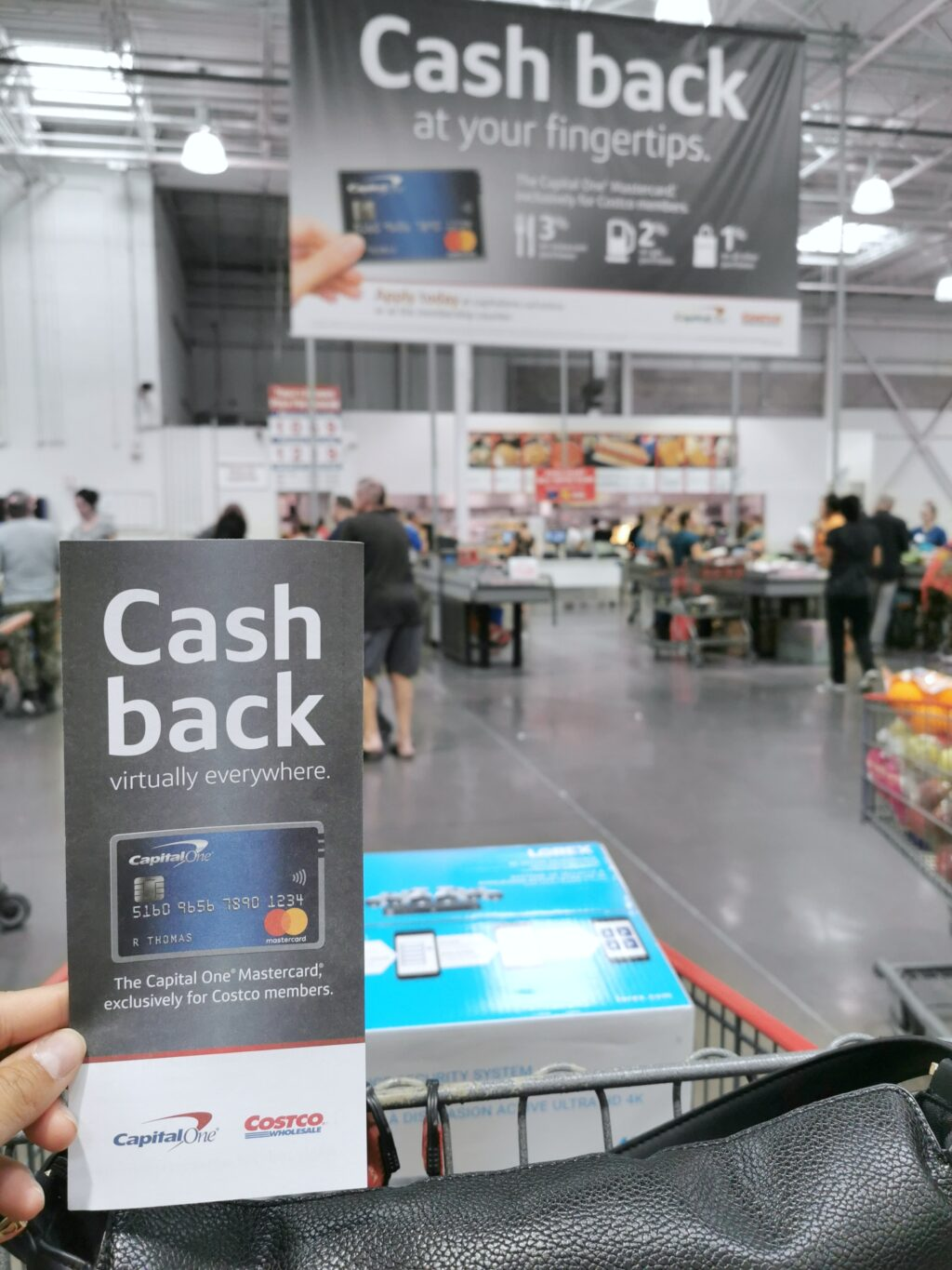 Shopping cart with Cash Back brochure showing Capital One's Mastercard. In the background, a large banner shows the same card.