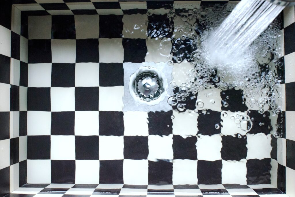 A checkered kitchen sink being filled up.